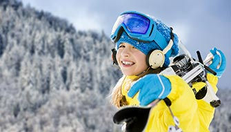 Girl in full ski equipment with her skiers on the shoulders
