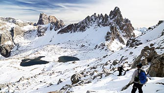 Snowy peaks of the Dolomites with excursionist in the foreground