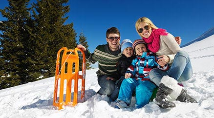 A smiling family with a toboggan surrounded by snow