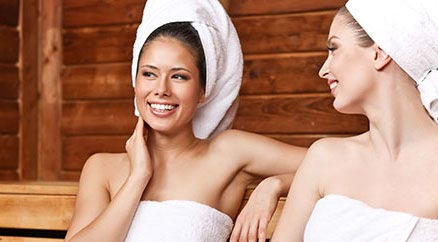 Two young women in the sauna with towels on their head