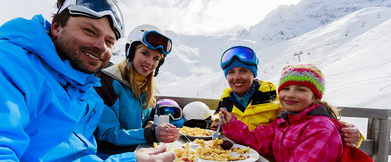 Family makes snack after skiing on the slopes of Plan de Corones