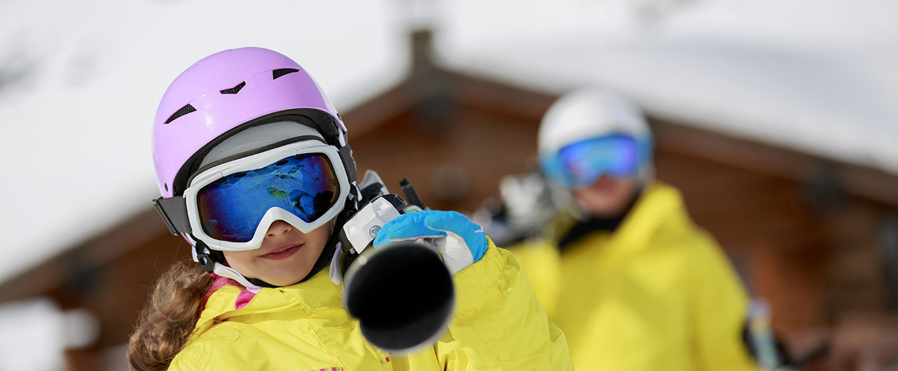 Young girl with yellow ski jacket and violet helm on a piste