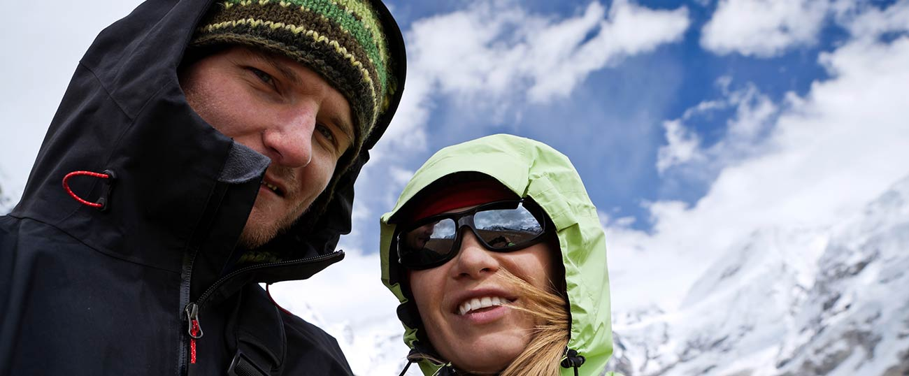 Photo of the heads of a couple with beanies and jackets in the mountains