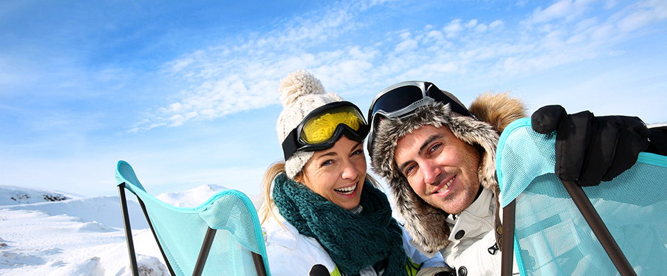 Smiling couple with wool jackets and beanies on two deckchairs next to a snowy slope