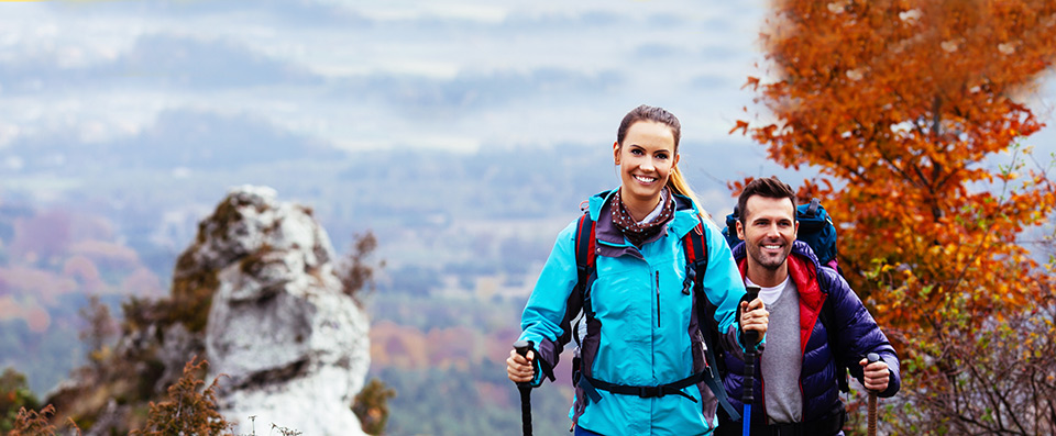 Young couple on a hiking trip and smiling: a wonderful yellow and red leaved tree in the background