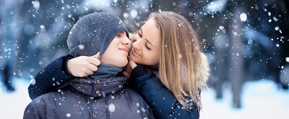 A boy and a girl are going to kiss each other while the snow falls