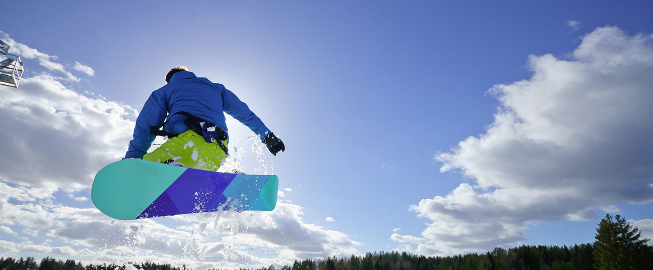 A snowboarder in the air after a jump on a sunny day