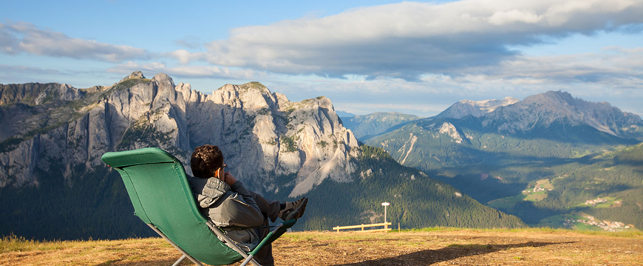 A man in a deckchair on the top of a mountain enjoying the panoramic view of Plan de Corones