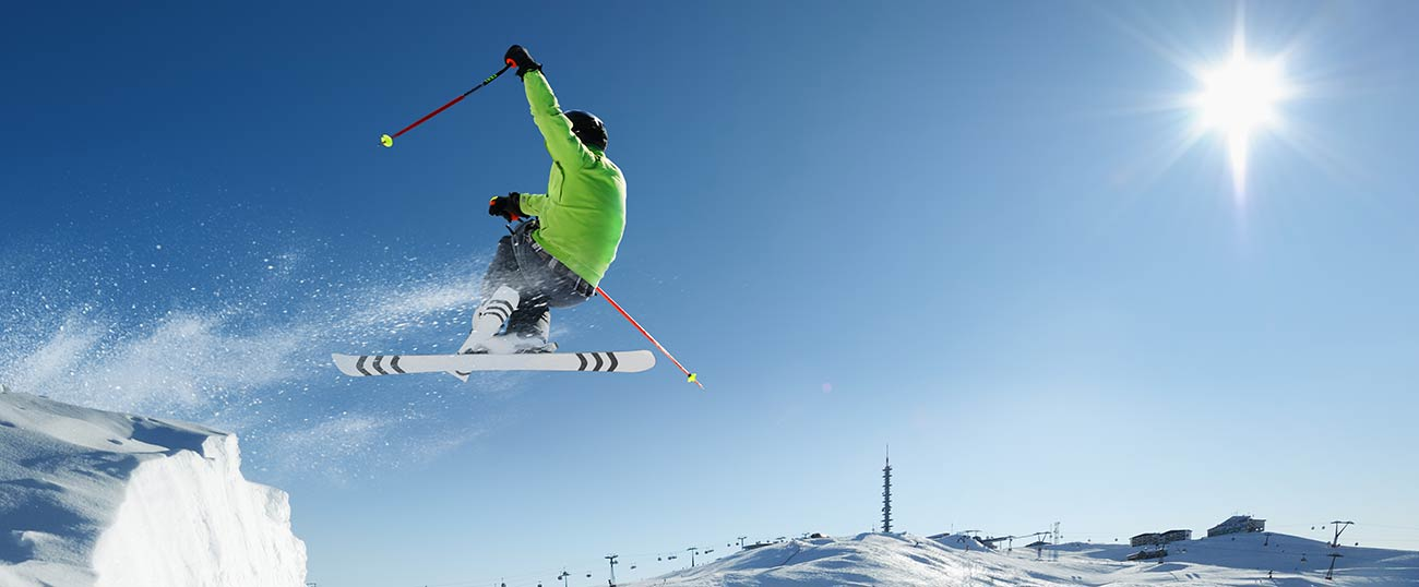 A skier in green ski jacket jumping backwards from a natural ramp