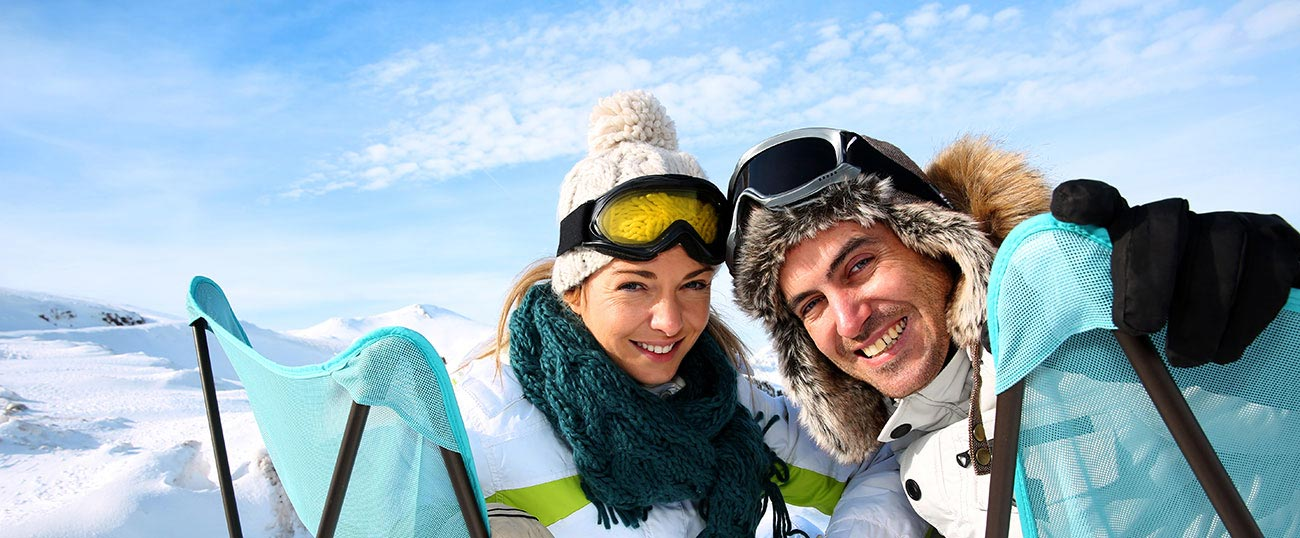 A couple in ski clothes posing for a photo on top of a snowy mountain