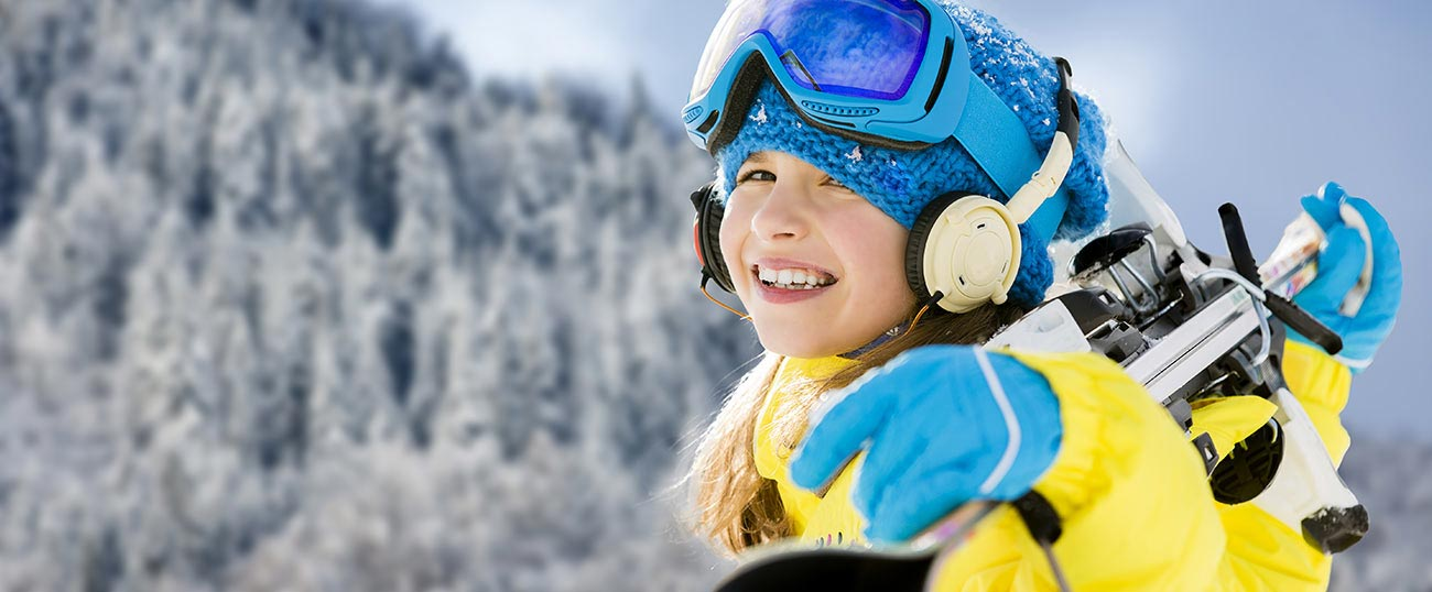Little girl with yellow jacket, gloves, hat and blue glasses with ski poles in hand