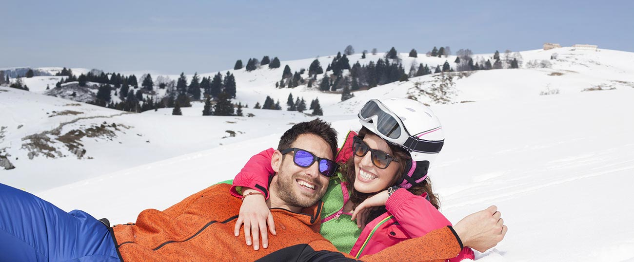 Couple with ski clothes and sunglasses having fun in the snow