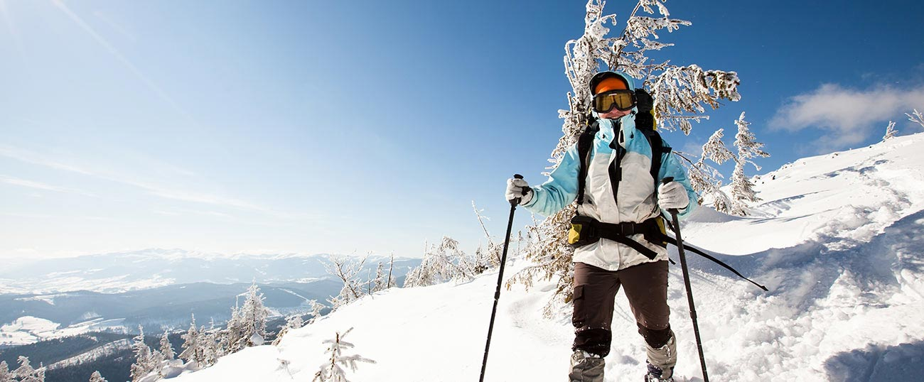 Person dressed in ski clothes walking on snow