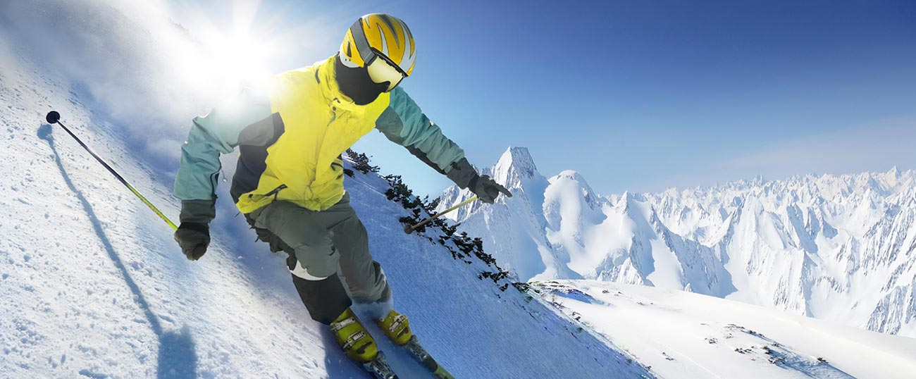 Expert skier with yellow jacket skis on steep snowy slope