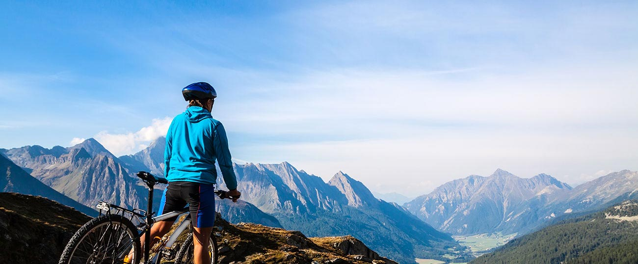 A mountain bike driver watches the stunning panorama view from Plan de Corones