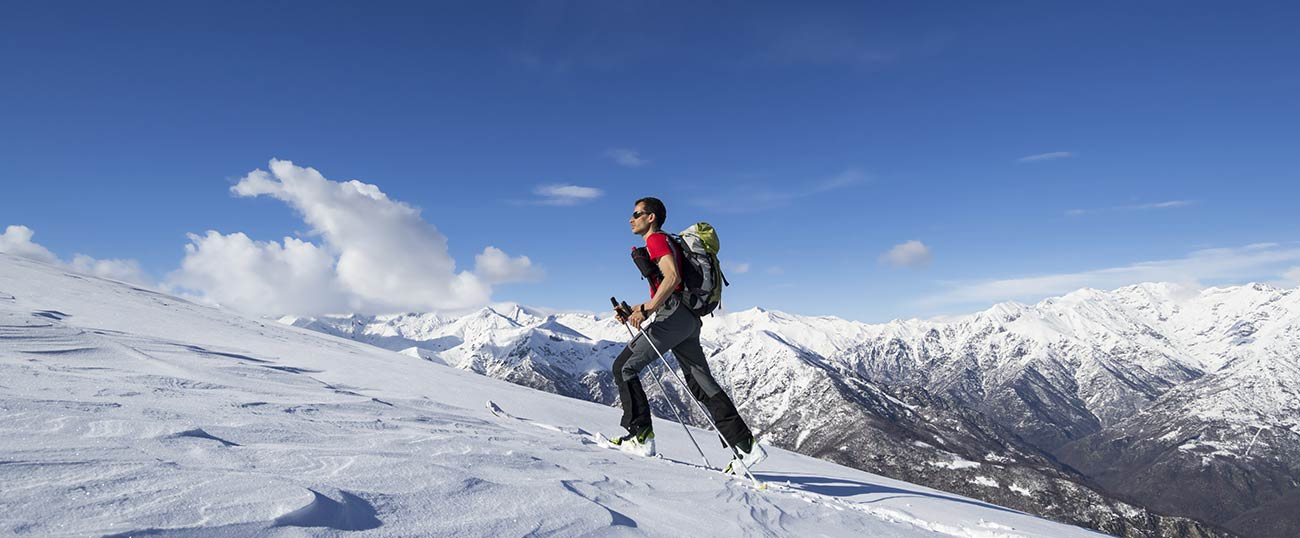 Alpine skier taking a walk and enjoying the view of the mountains