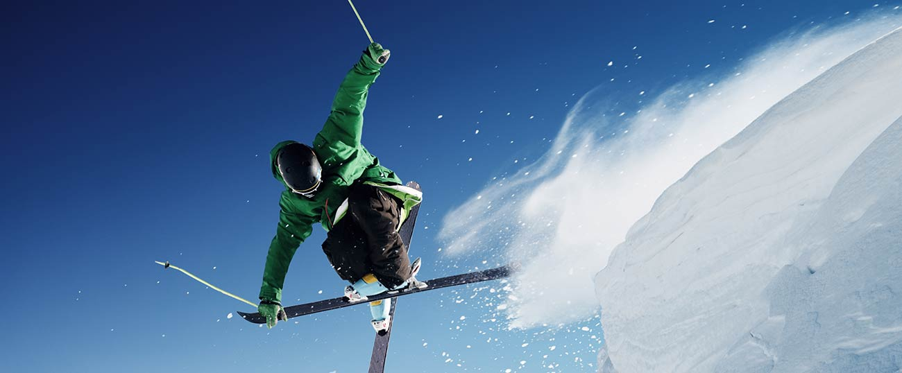 A skier jumping in the air and crossing its skis