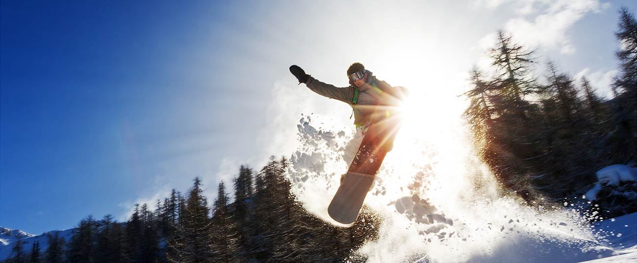 A jumping snowboarder leaves a cloud of powder snow in the air