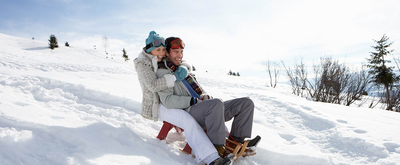 A couple on a toboggan ride surrounded by mountains of snow