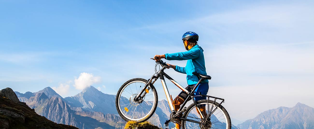 A biker with a mountain bike on the top of a mountain enjoying the panoramic view
